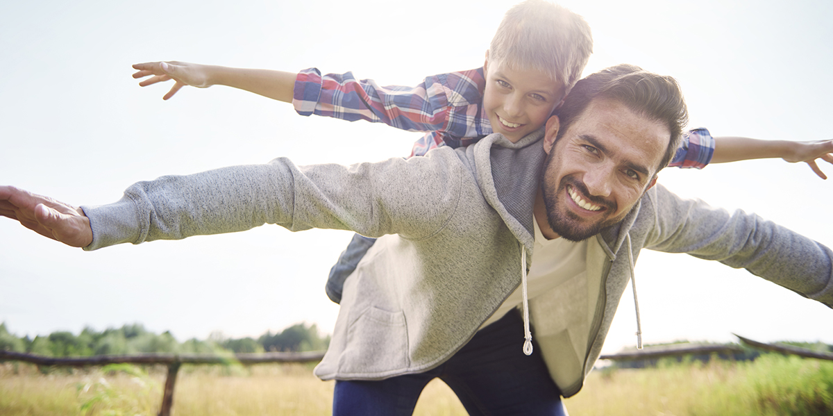 A father and his young son on his back with their arms out playing airplane