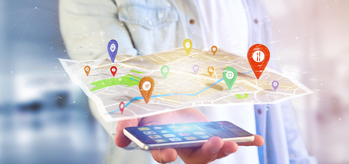 Person with smartphone in hand showing geofencing data